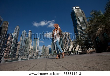 Smiling girl in hijab covering her eyes with happiness in Dubai Marina