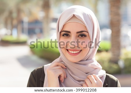 Smiling girl in hijab covering her eyes with happiness in Dubai Marina - stock photo