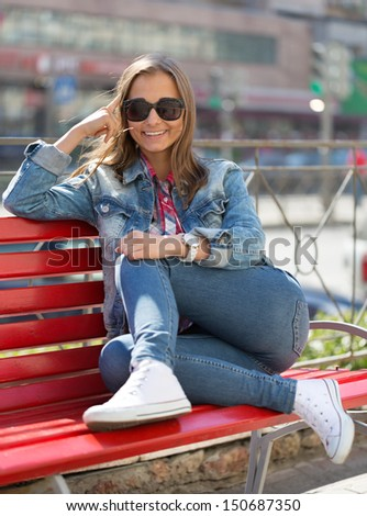 smiling girl in jeans sitting on a bench on a city street - stock photo