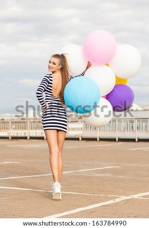 smiling girl in open-back black and white striped short dress and white high top sneakers with bunch of multicolored balloons turns back - stock photo