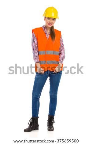 Smiling girl in orange reflective vest, yellow hardhat, lumberjack shirt, jeans and black boots. Full length studio shot isolated on white. - stock photo