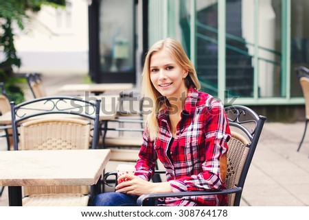 Smiling girl in plaid shirt sitting at the cafe outdoor