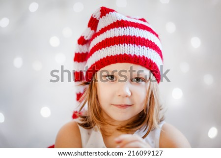 Smiling girl in red and white Santa hat