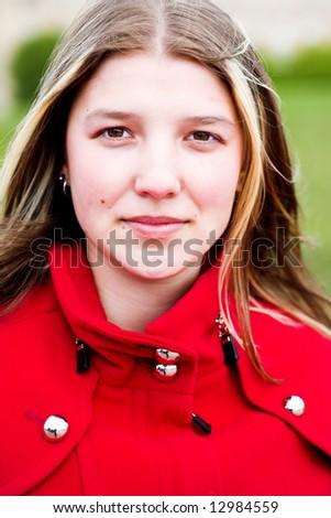 Smiling girl in red coat portrait outdoor - stock photo