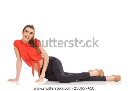 Smiling girl in red top, black jeans and high heels leaning on the floor and looking up. Full length studio shot isolated on white. - stock photo