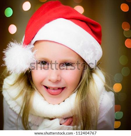 Smiling girl in santa hat on the background of Christmas lights.