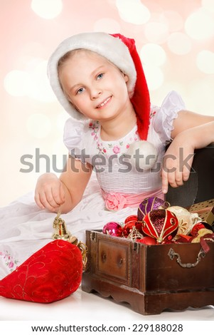 Smiling girl in Santa hat with Christmas decorations