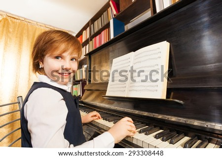 Smiling girl in school uniform playing the piano with notes during lesson indoors - stock photo