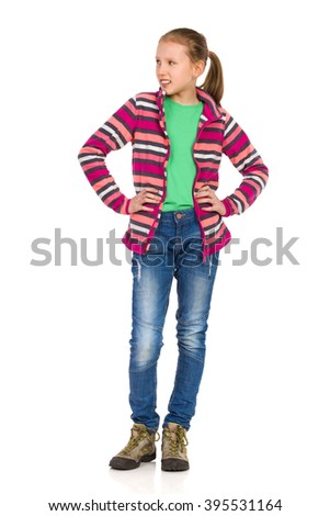 Smiling girl in striped fleece blouse, jeans and hiking boots standing with hands on hip and looking away. Full length studio shot isolated on white.