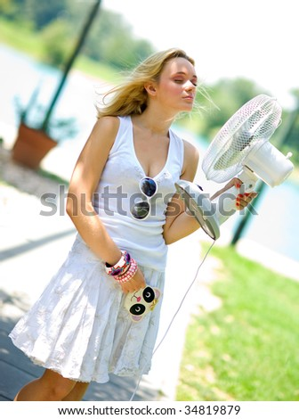 smiling girl in summer dress cooling herself with fan - stock photo