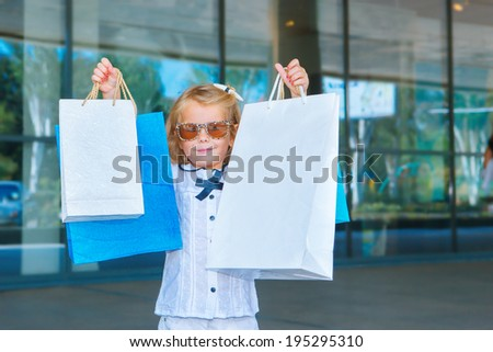 Smiling girl in sunglasses holding shopping bags in hands - stock photo