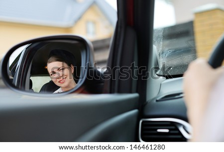 Smiling girl in the car looking in the mirror  - stock photo