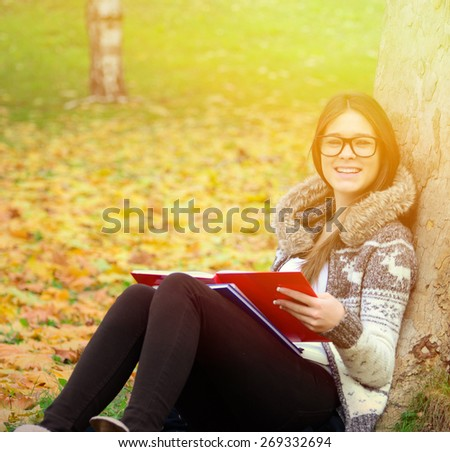 Smiling girl learning in nature - stock photo