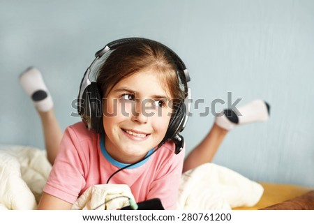 smiling girl listens to music - stock photo
