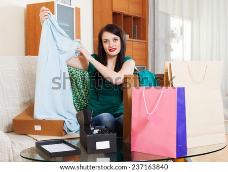 Smiling girl looking at purchases at her home