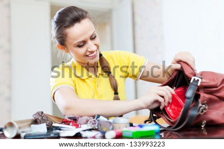 Smiling girl looking for something in handbag at table in home
