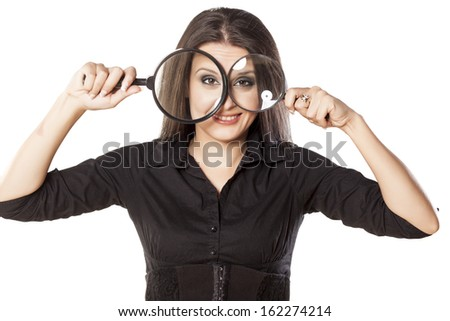 smiling girl looking through a magnifying glass - stock photo