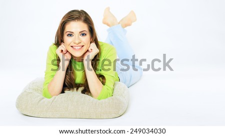 Smiling girl lying on a floor with crossed legs. Isolated white background young woman full body portrait. - stock photo