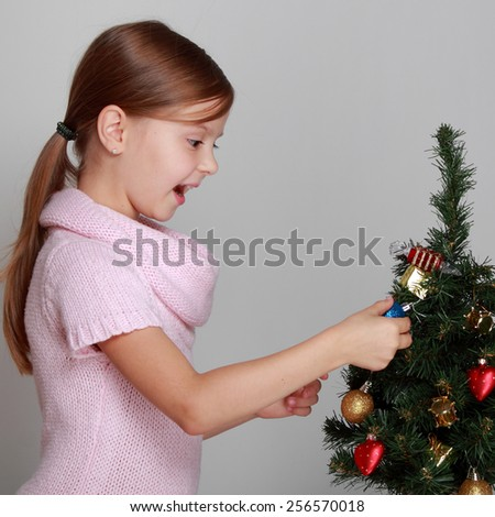 Smiling girl near a Christmas tree - stock photo