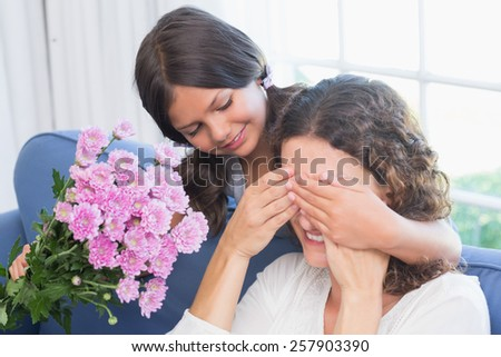 Smiling girl offering flowers to her mother in the living room - stock photo