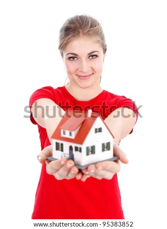 Smiling girl offering us a miniature house, new home concept - stock photo