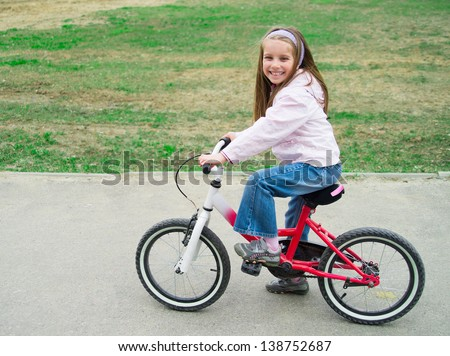 Smiling girl on a bicycle in summer park outdoors