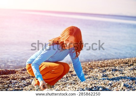 smiling girl on sea beach on the blue water background - stock photo