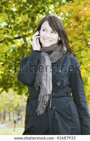 Smiling Girl on the phone in the park. - stock photo