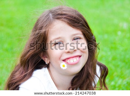 Smiling girl outdoors with a daisy flower in her mouth - stock photo