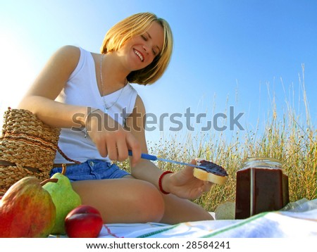Smiling girl outdoors with a picnic breakfast of fruit, bread and jam.