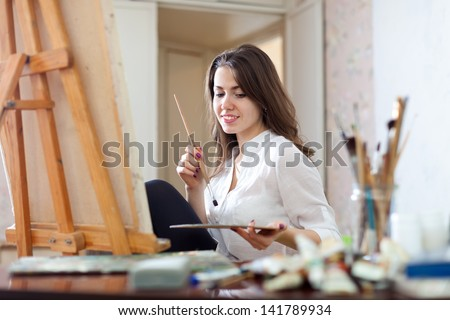 Smiling girl paints on canvas with oil colors - stock photo
