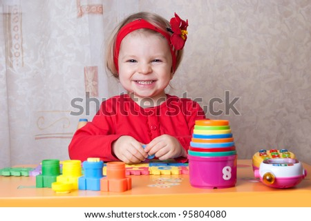 Smiling girl playing at table in nursery - stock photo