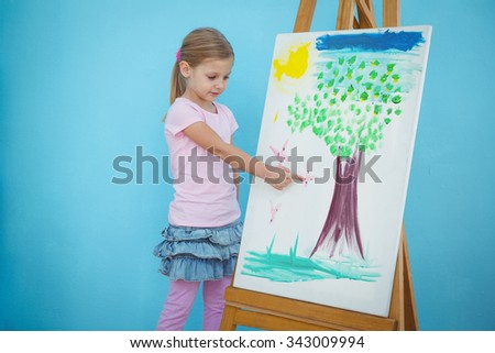 Smiling girl pointing to her picture on an easel - stock photo