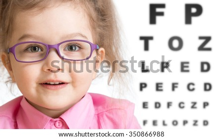 Smiling girl putting on glasses with blurry eye chart behind her - stock photo