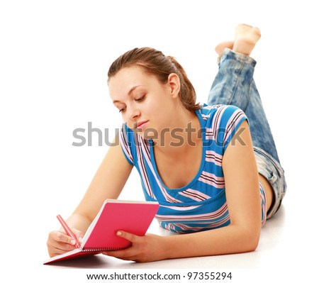 Smiling girl reading and making notes while lying on floor isolated on white background