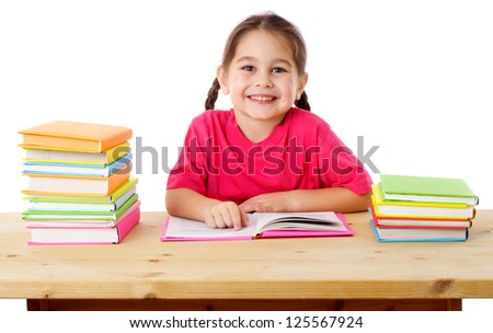 Smiling girl reading the books on the desk, isolated on white - stock photo