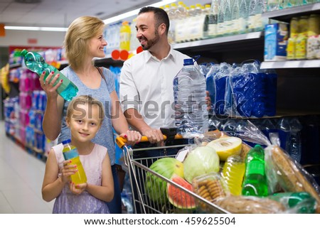 Smiling girl selecting non-alcoholic beverage in plastic bottle in food store - stock photo