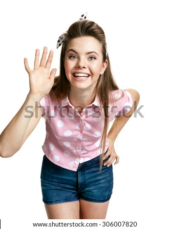 Smiling girl showing her hand up, greeting gesture / photo of young cheerful brunette woman over white background, positive emotions - stock photo