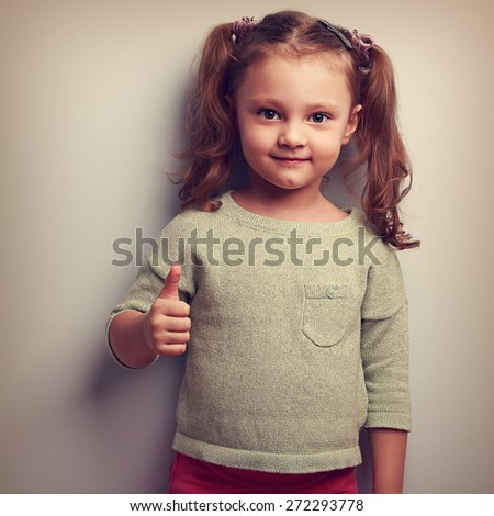 Smiling girl showing thumb up sign and looking happy. Vintage closeup portrait - stock photo