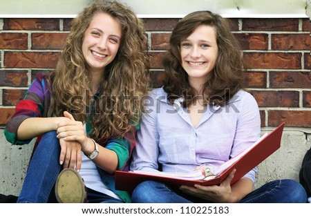 Smiling girl sit outside and studying together
