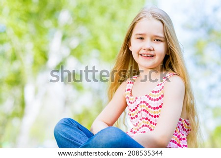 smiling girl sitting in the grass on a summer park - stock photo