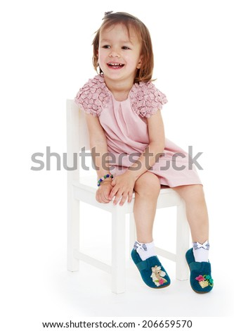 Smiling girl sitting on a chair, white background. Happy childhood, carefree childhood concept. - stock photo