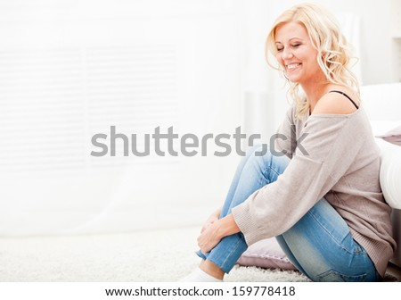 Smiling  girl sitting on carpet - stock photo
