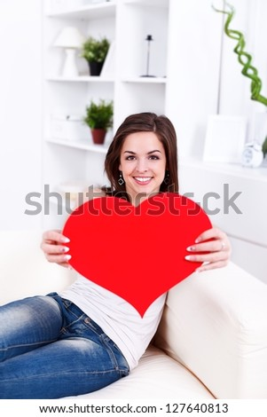 Smiling girl sitting on the sofa offering a big paper heart to us