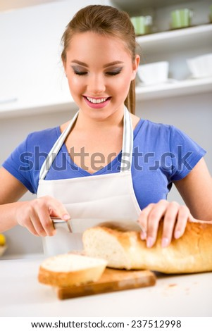 Smiling girl slicing bread on a cutting board in kitchen