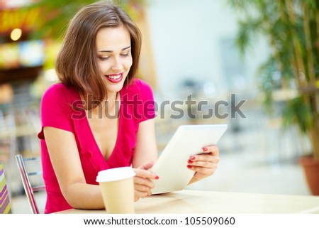 Smiling girl spending time in a street cafe using digital tablet