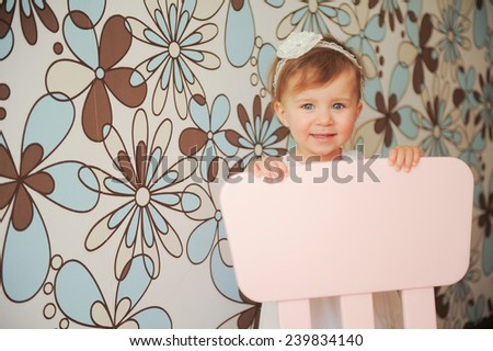 smiling girl standing behind chair - stock photo