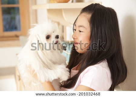 smiling girl staring at a puppy