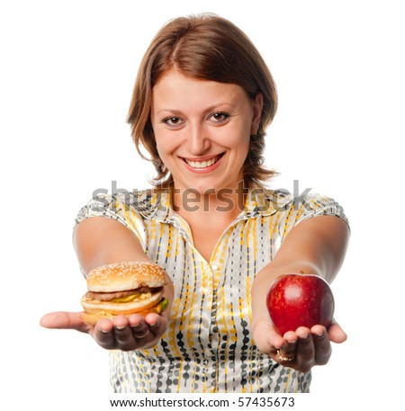 Smiling girl stretches apple and hamburger