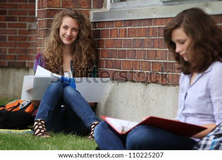 smiling girl studying outside with her friend